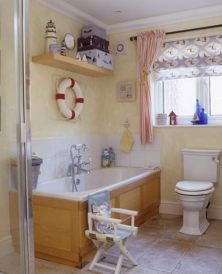 Childs bathroom, nautical theme, life buoy, lighthouse, pine surronded bath, red and white striped curtains. Pub orig IH 05/2007 Real home