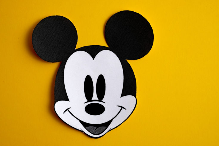 RUSSIA, ST.PETERSBURG - NOVEMBER 19, 2018: Black and white face of Mickey Mouse out of paper on a yellow background.