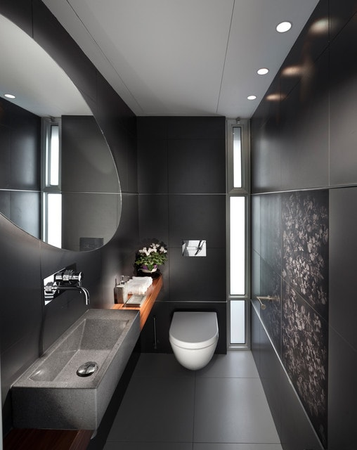 Trendy bathroom photo in Other with a wall-mount toilet, black walls and an integrated sink