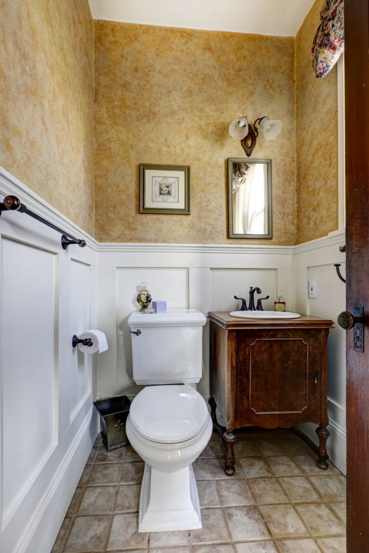 White and mocha bathroom interior with tile floor and antique vanity cabinet
