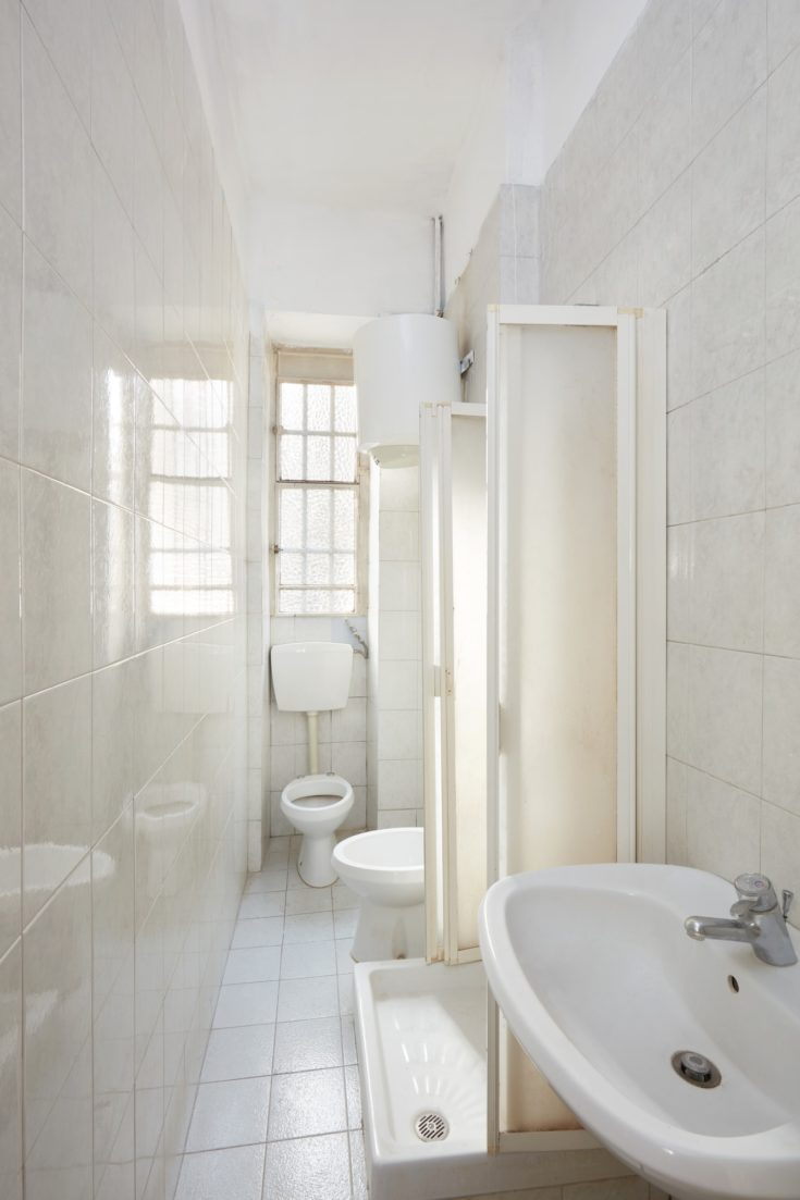 Old bathroom interior with tiled floor and walls