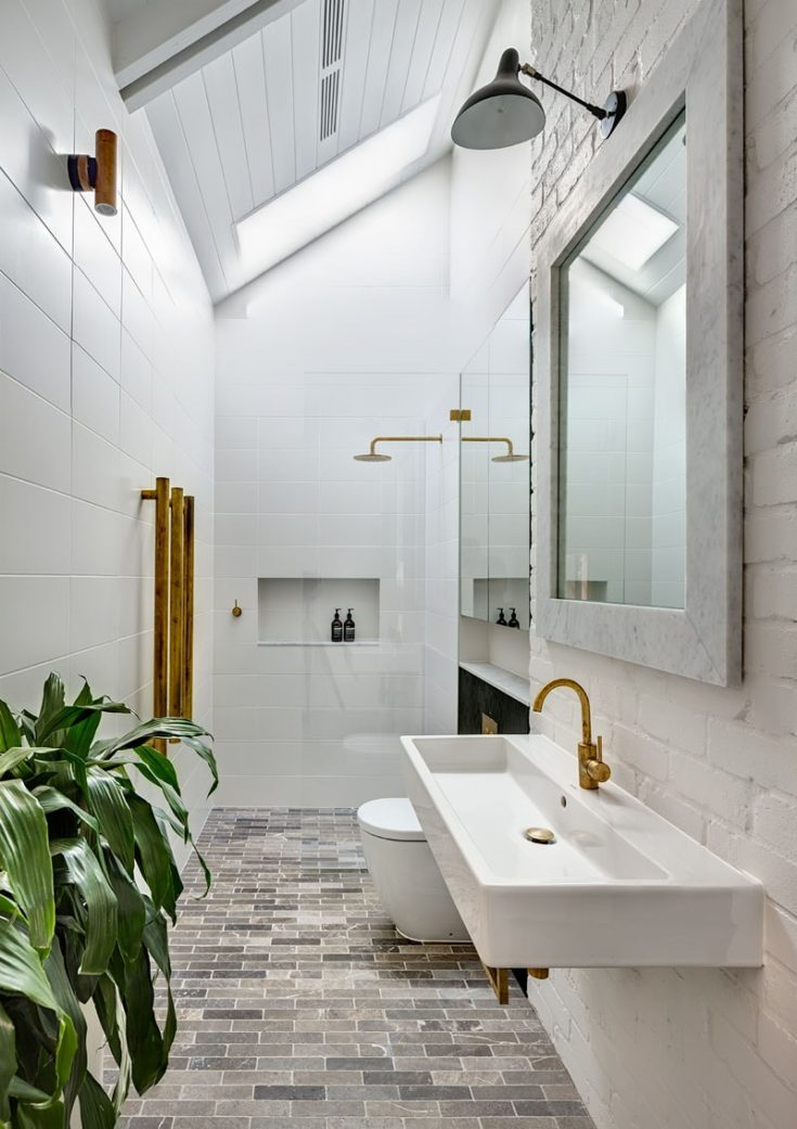 In the bathroom, white walls and ceilings make the brass accents and black cabinetry stand out. A skylight provides plenty of natural light to the space.