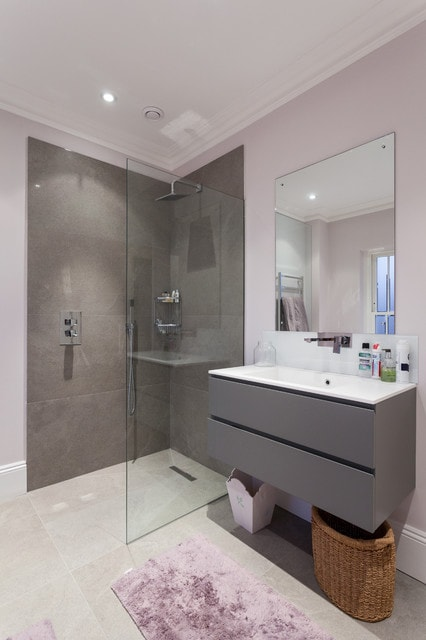 Trendy gray tile bathroom photo in London with an integrated sink, flat-panel cabinets, gray cabinets and purple walls