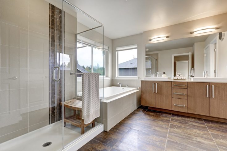 White modern bathroom interior in brand-new house. Double sink vanity with large mirror, walk-in shower, white bath tub and brown tile floor. Northwest, USA
