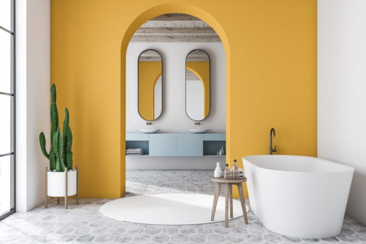 Interior of modern bathroom with white and yellow walls, tiled floor, white bathtub and double sink on blue countertop with mirrors in background. 3d rendering