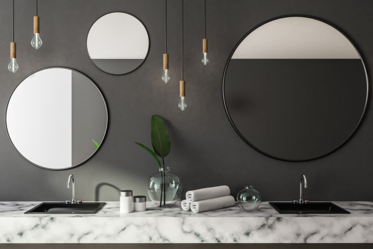 Double sink in marble countertop in gray bathroom interior with round mirrors and rolled towels. Concept of luxury hotel, spa, house. 3d rendering