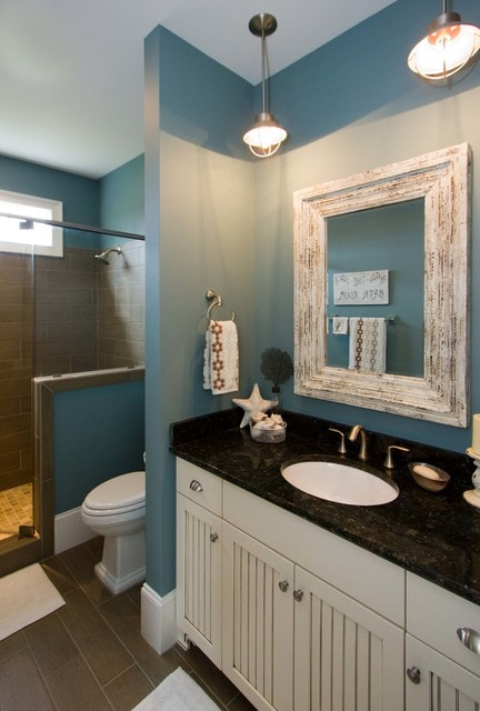 Example of a beach style brown tile alcove shower design in Wilmington with an undermount sink, recessed-panel cabinets and beige cabinets