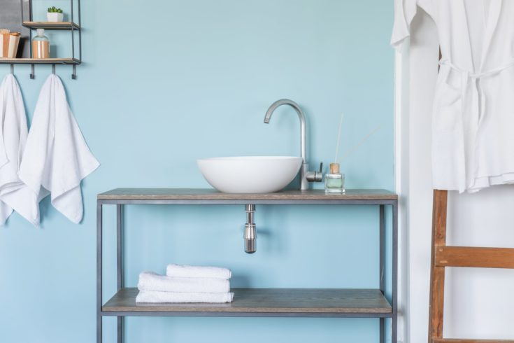 Interior of clean bathroom with sink near color wall