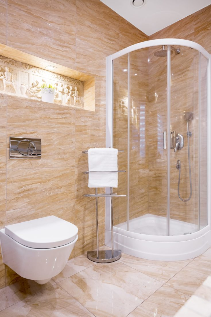 Shower in modern bathroom with beige marble and sculpture on wall