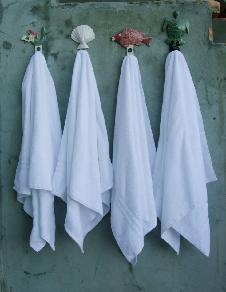 Four crisp white towels hang on beach themed hooks in an outdoor shower area