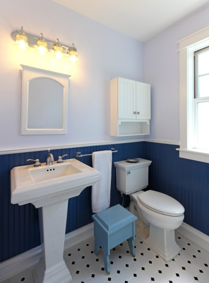 Bathroom with sink and toilet with blue walls and tile floor.