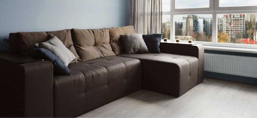 Brown couch beside the window with throw pillows
