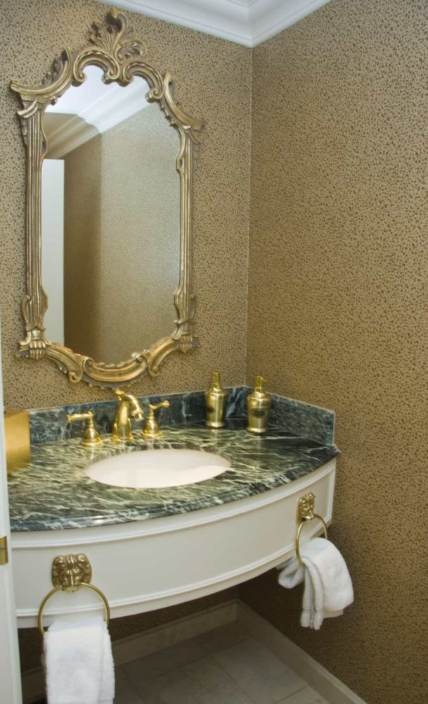Two brass taps on marble plate sink and baguette framed mirror