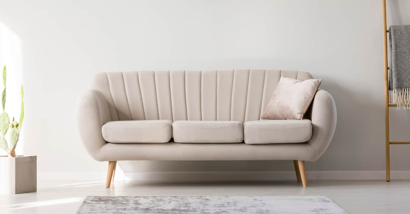 Cream white couch with a wooden foot.