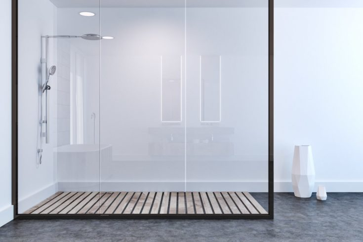 White wall bathroom interior with a concrete floor, a shower stall