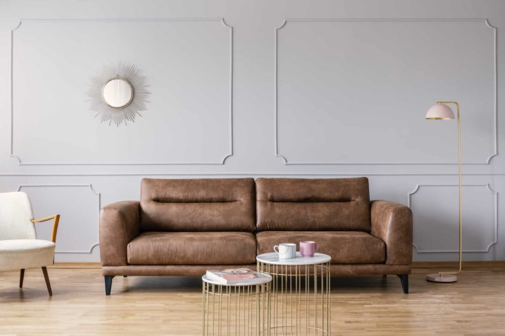Gold tables in front of leather sofa in grey elegant living room interior with mirror and lamp. Real photo