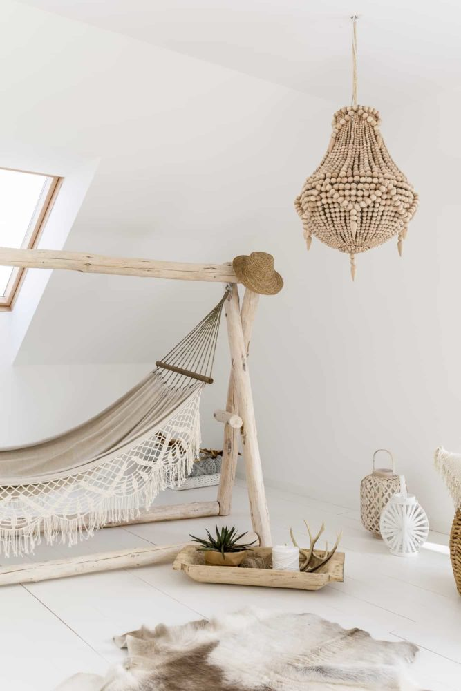 Decorative chandelier with wooden accessories in living room with hammock and fur on floor