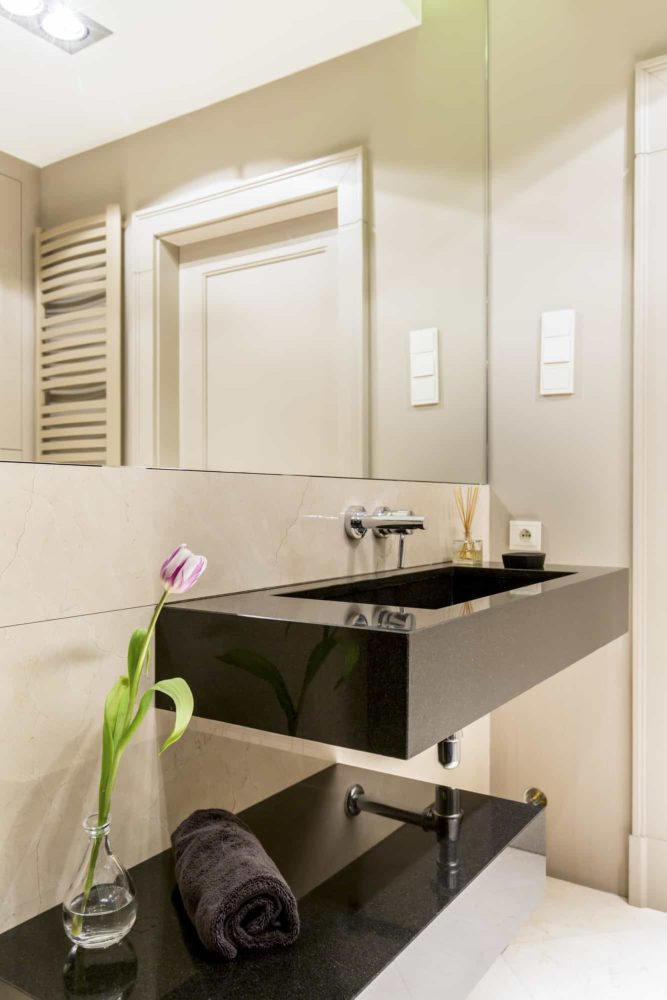 Modern white bathroom with dark sink and a large mirror