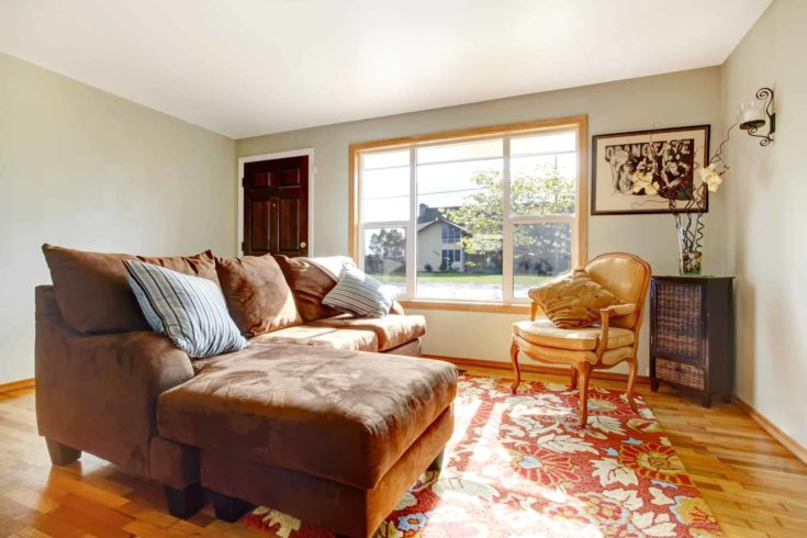 View of living room with comfortable sofa and antique chair