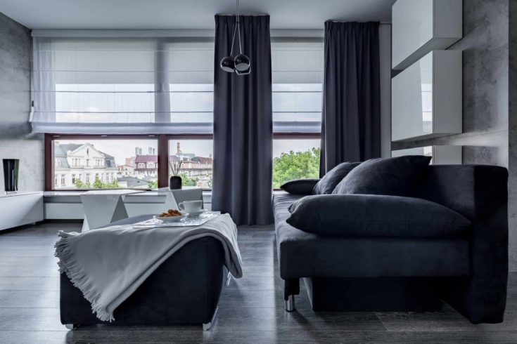 Contemporary living room with gray couch, pouf and big windows