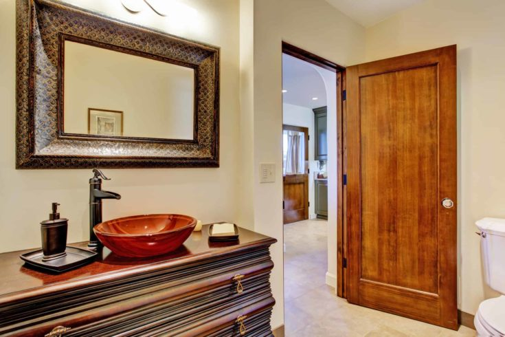 Bathroom interior in luxury house. View of rich bathroom vanity cabinet with vessel sink and mirror