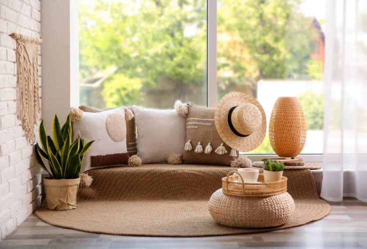 Comfortable place for rest with cushions near window indoors