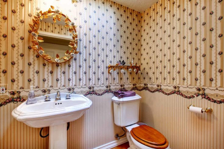 Old fashioned style bathroom with wallpaper, decorated gold mirror and wall shelf