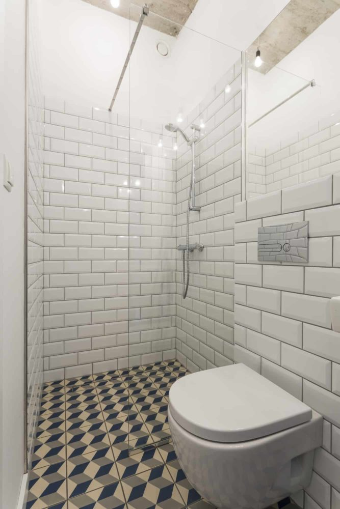 Modern bathroom with walls decorated with brick-resembling white tiles and a glass shower enclosures