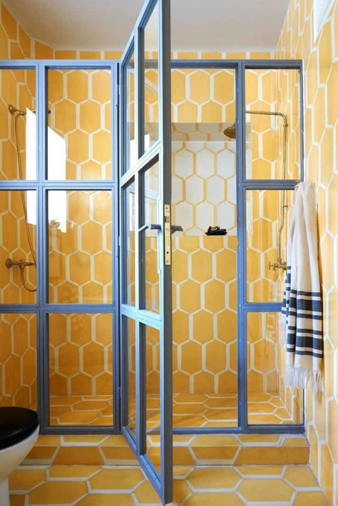 The bathroom in this Moroccan home is covered in warm yellow Popham Design tiles