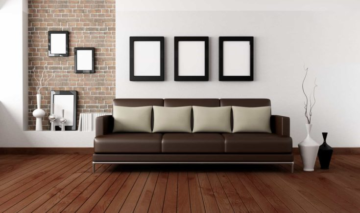 brown sofa with pillow in front a white wall and brick niche