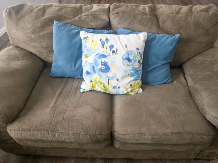 Vibrant colorful plain and printed throw pillows on living room couch of a home.