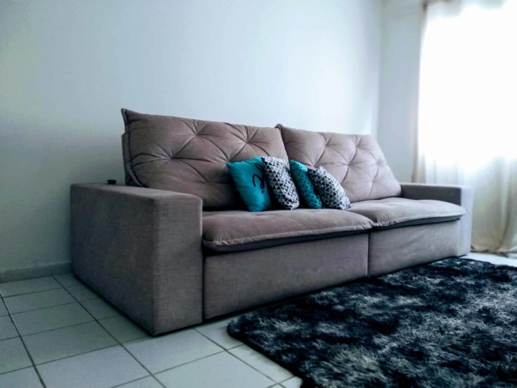 Gray couch with pillows and black carpet