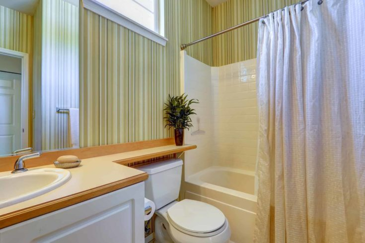 Bathroom interior in american house. Stripped wallpaper, tile wall trim and light brown counter top