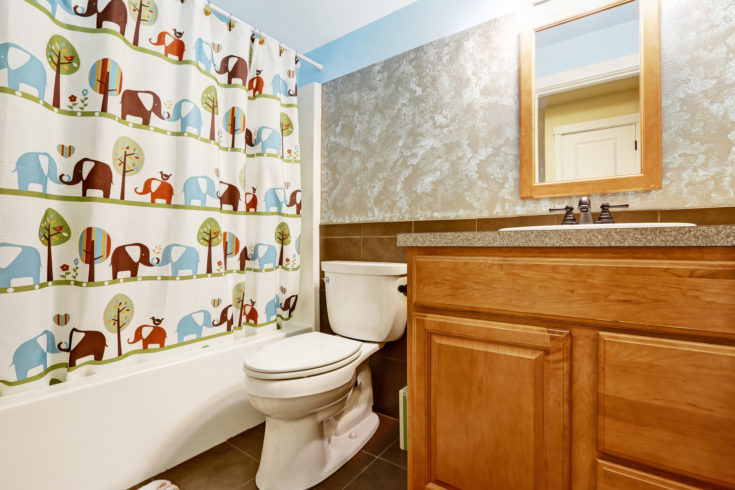Bathroom interior with cheerful curtain and wooden cabinet with small mirror