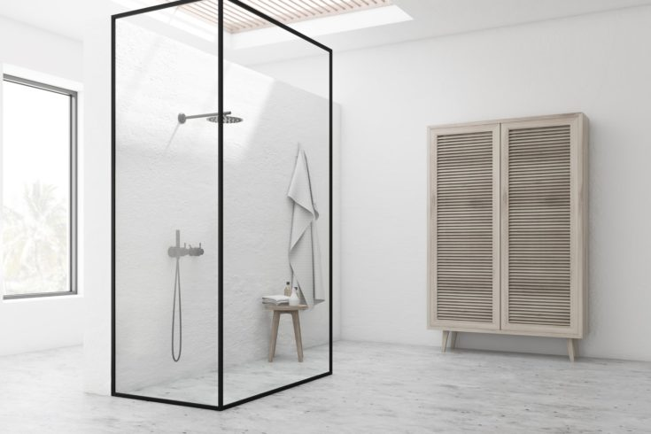Corner of stylish bathroom with white walls, stone floor, shower stall with glass walls