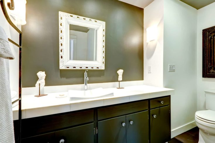 Bathroom in white and olive tones. View of dark wooden vanity cabinet with mirror