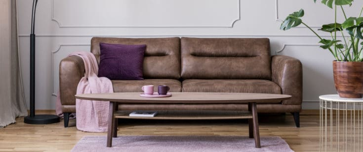 Wooden table in front of leather sofa with pink blanket.