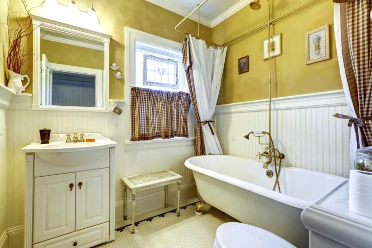 Yellow old bathroom interior with white plank paneled wall trim and antique vanity and bath tub