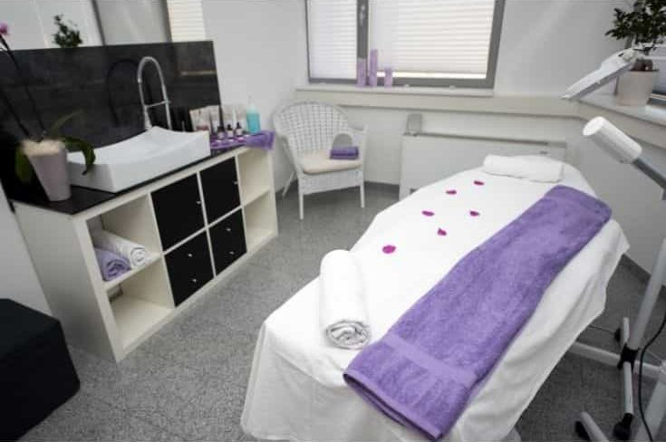 Massage table and equipment in modern beauty salon.
