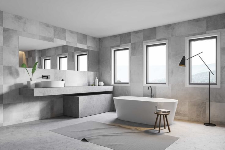 Corner of gray tile bathroom with stone floor, white bathtub, sink standing in on stone counter and three narrow windows. 3d rendering