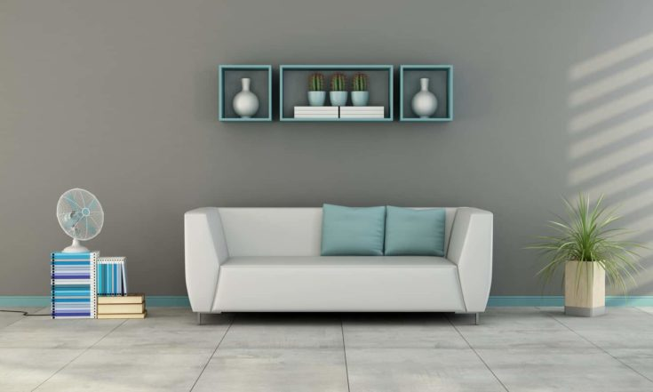 Contemporary living room with white sofa with blue cushion and fan on books - 3D Rendering