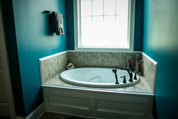 Dark teal painted bathroom with large garden bathtub and a window and a hanging towel